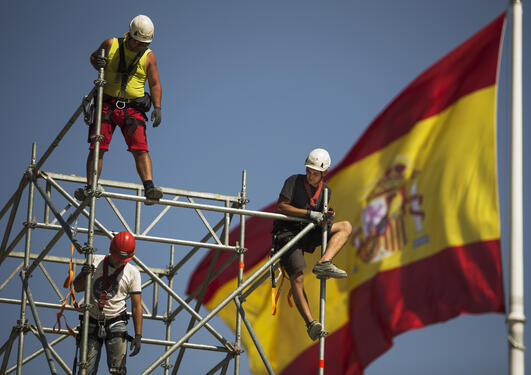 Workers on scaffolding in front of a Spanish flag, used to accompany article about migration from Spain to Norway.