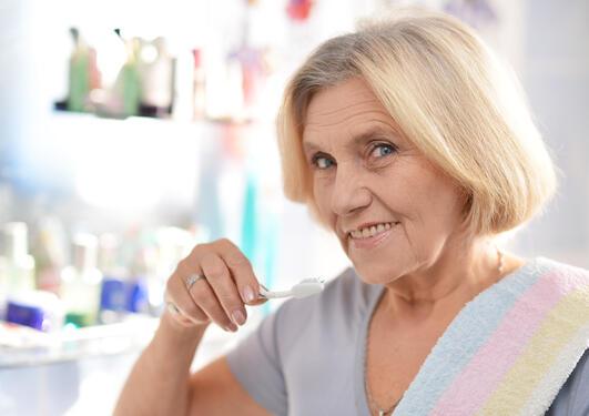 Illustrasjonsfoto av eldre kvinne som puser tennene.