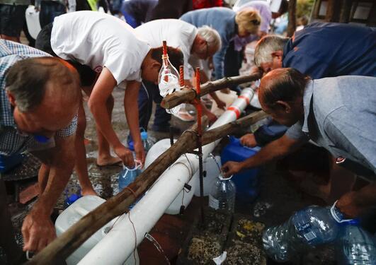 Bilde av innbyggjarar i Cape Town som hentar vatn frå vannstasjon.