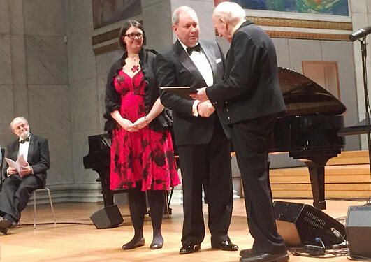 Akslen and Wik on the stage at the University Aula in Oslo, receiving the grant by Olav Thon.