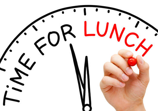 """Del av en klokke og en hånd som skriver """"Time for lunch"""""""