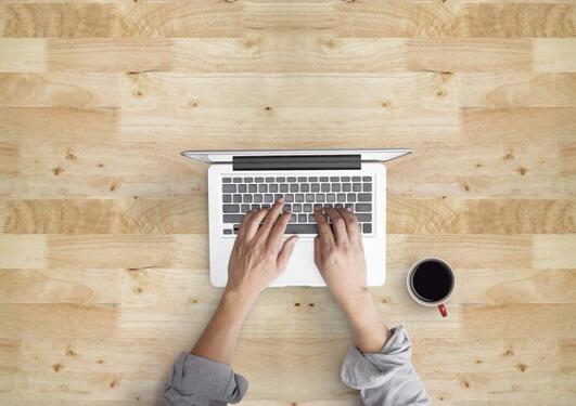 Hender ovenfra som jobber på en laptop