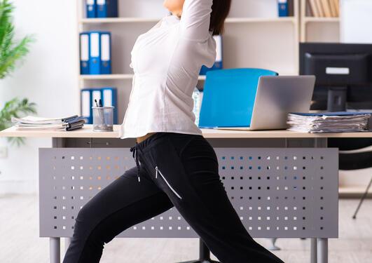 Bildet viser dame som tøyer på kontoret