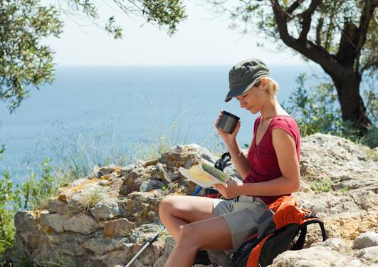 Bildet viser dame som leser kart og drikke kaffe i naturen