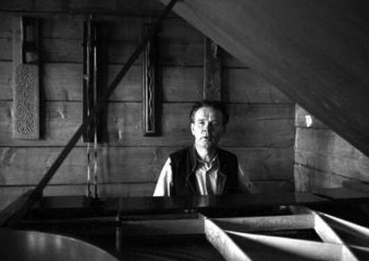 Et sort hvitt bilde av komponisten Geirr Tveitt som sitter ved sitt flygel.