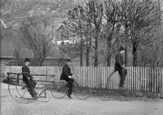 Tre menn på ulike historiske sykler