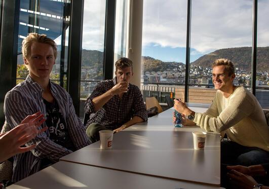 Tre unge mannlige studenter diskuterer