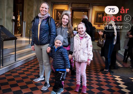 En familie på fire vei inn på Universitetsmuseet. Oppe til høyre står det 75 år med tanker.