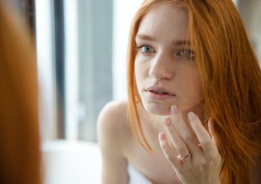 Ung kvinne ser seg selv kritisk i speilet