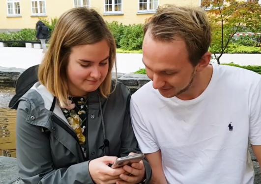 Jente og gutt sitter foran Sydneshaugen skole og ser sammen på mobiltelefon for å teste hubro chatbot