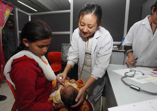 Temsunaro Rongsen-Chandola administering an oral rotavirus vaccine in India