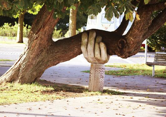 Wooden hand holding a tree
