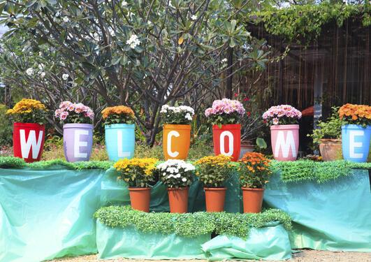 Bildet viser blomsterpotter med bokstaver som danner ordet welcome