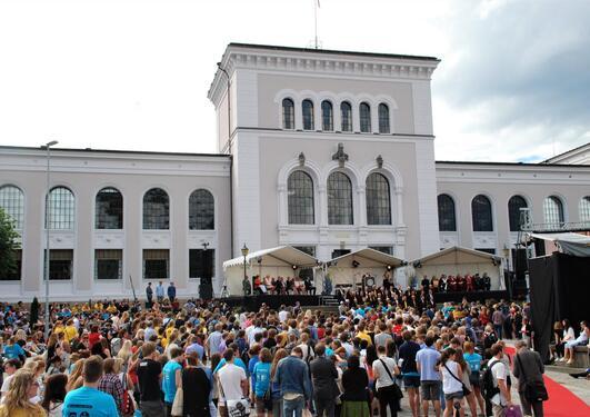 Mange nye studenter foran en scene, med Universitetsmuséet i bakgrunnen.