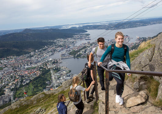 Several students climbing up mount Ulriken with the city scenerey behind them
