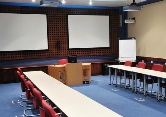 Tomt konferanselokale med stoler, bord, to projektorer
