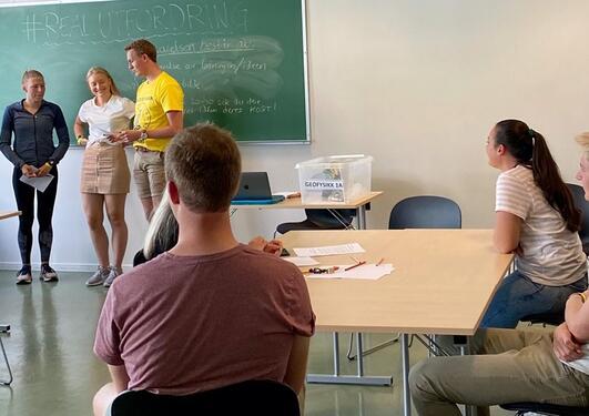 Fire studenter presenterer noe foran en tavle. Andre studenter sitter rundt et bord og ser på.