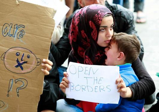"""Kvinne med barn på flukt. Hun holder et skilt der det står """"Open the borders"""""""