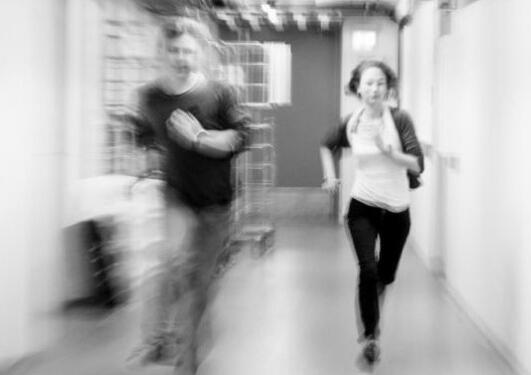 Bildet viser to personer som løper i en gang.