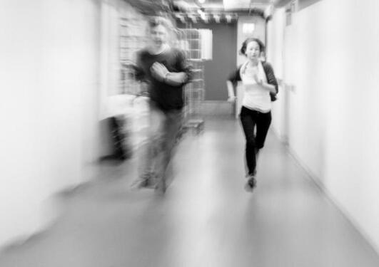 To personer som løper, litt ute av fokus. Svart-hvitt bilde