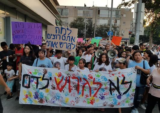 "arge Hebrew banner reads, ""Don't deport children."" Smaller sign reads, ""Why do you want to deport me?"""