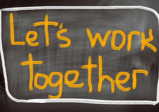 """Ordene """"let's work together"""" på en skoletavle"""