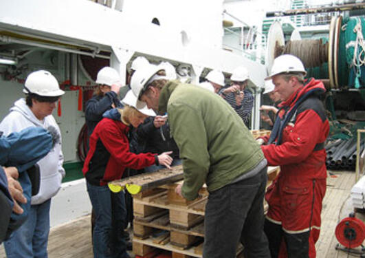 scientists grouped around a newly opened sediment core
