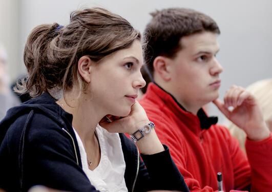 Kvinnelig og mannlig student under forelesning