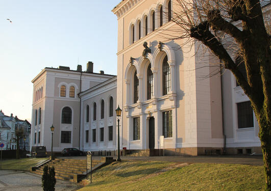 Universitetsmuseet fra side ved inngangsparti. morgensol og blå himmel