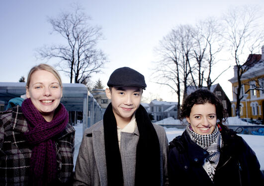Three international students smiling at the camera with snow in the background