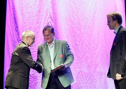 Arno Vigmostad og Arnstein Bjørke vert gratulerte av rektor Sigmund Grønmo.