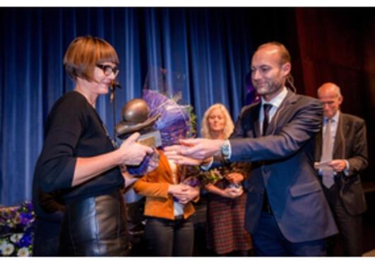 Statssekretær Knut Olav Åmås deler ut prisen til forskar Marta Ebbing.