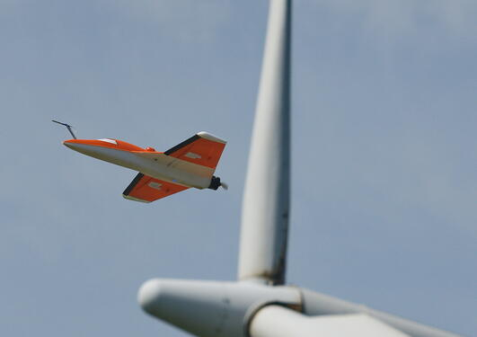 Et ubemannet obsrvasjonsfly foretar målinger ved  vindmølleparken Nøjsomhed...